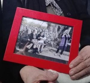 Emilia Kamvysi, simbolo dell'accoglienza dell'isola di Lesbo ai migranti, tiene in mano la foto in cui fu immortalata, Skala Sykaminias, 13 febbraio 2016. La 'nonnina', che in paese chiamano Militza, fu immortalata in una foto diventata subito virale sul web, mentre dava il biberon al figlio neonato di una giovane profuga. ANSA/ LAURENCE FIGA'-TALAMANCA