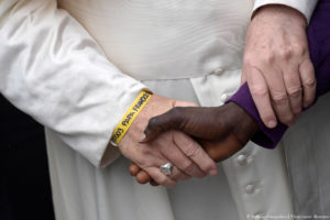 Pope Francis wears a yellow plastic ID bracelet as he shakes hand with a man during a visits at a migrant's reception centre during a pastoral visit in Bologna, Italy October 1, 2017. Osservatore Romano/Handout via Reuters ATTENTION EDITORS - THIS IMAGE WAS PROVIDED BY A THIRD PARTY. NO RESALES. NO ARCHIVE. TPX IMAGES OF THE DAY